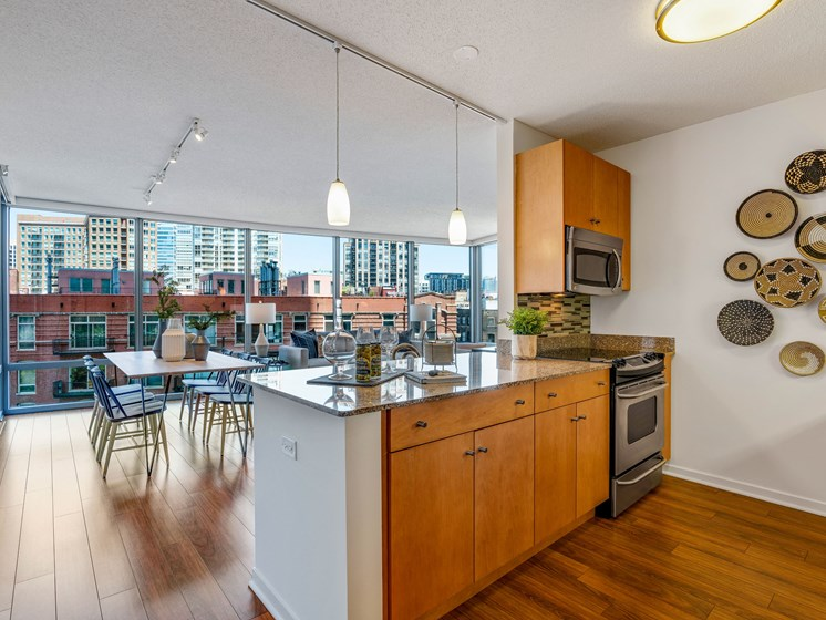 Kitchen photo with stainless steel appliances, wall decor, and a view of the living room