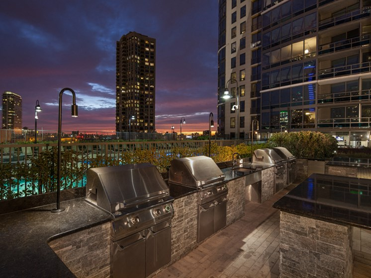 Outdoor grilling area at dusk with slight sunset and Kingsbury Plaza facade in the background