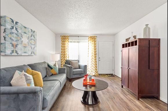 Living Room View With Hardwood Floors And Large Window Raindance Apartments