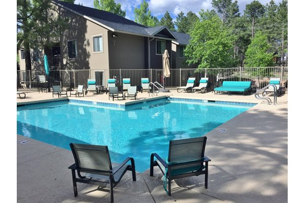 Swimming Pool with Ample Lounge Chairs at Woodlands Village Apartments in Flagstaff, AZ