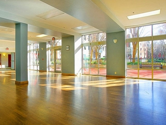 Photo of the community space with hardwood floor and large windows.