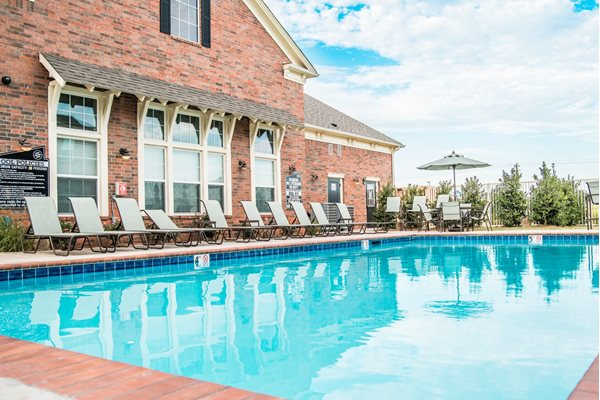 Resort-style swimming pool with expansive sundeck at Westmoore Apartments in Oklahoma City, OK