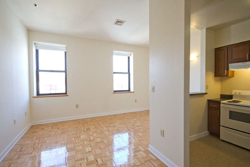 living room and partial kitchen view with hardwood floors and white walls