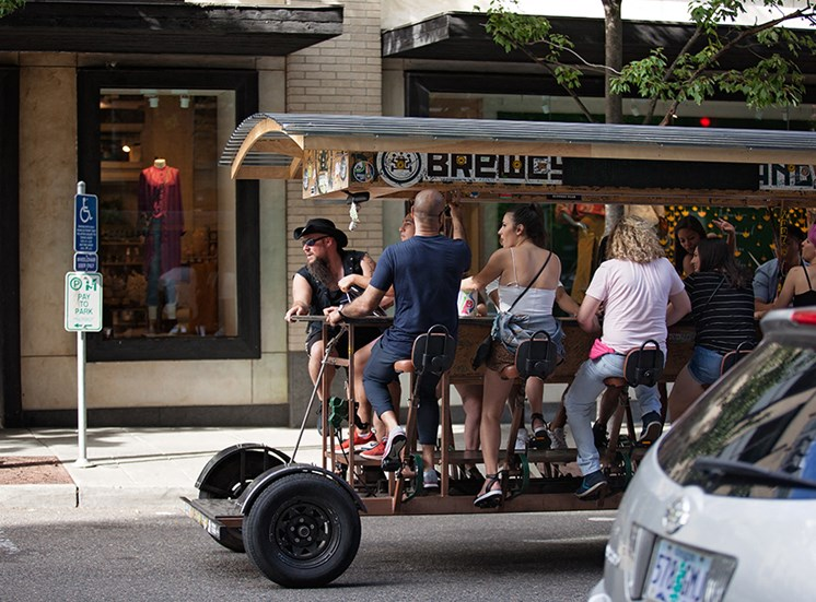 group of people pedal biking on booze tour through city