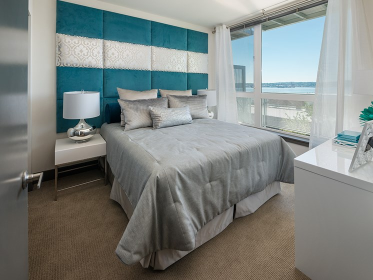 ArtHouse Downtown Seattle WA Apartments - Bedroom With Carpeting, Modern Blue Decor and Large Window With Ocean Views