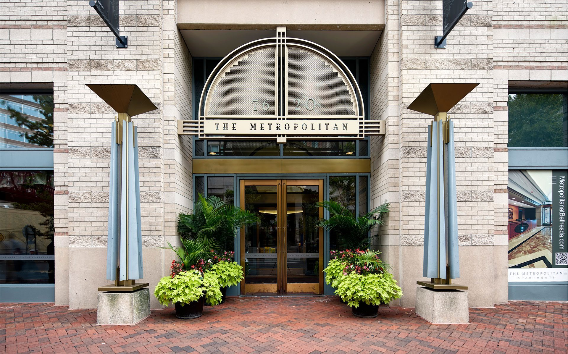 Front doors of The Metropolitan located at 7620 Old Georgetown Road, with brick entranceway and green plants.