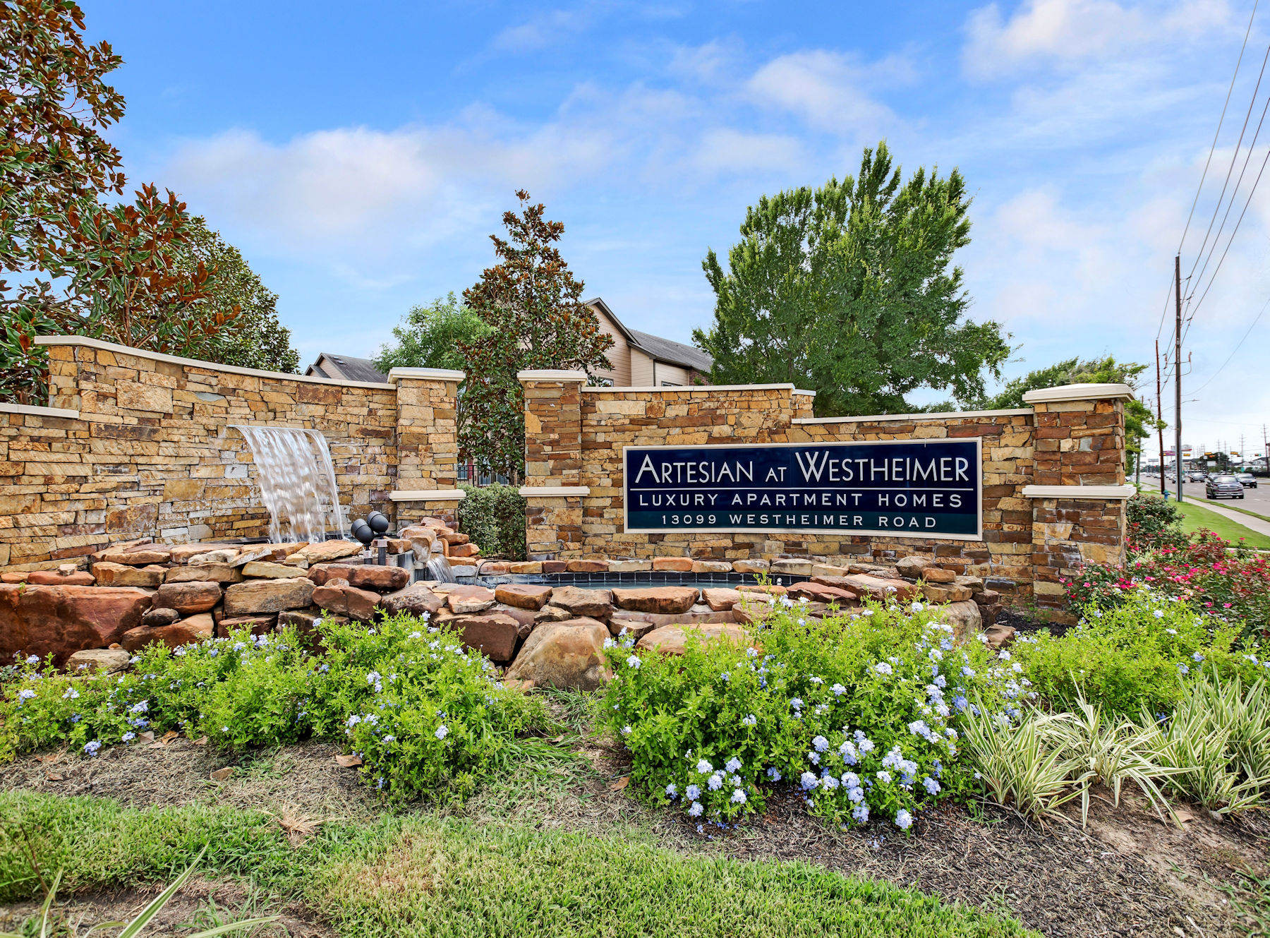Beautiful stone entry sign with waterfall and landscaping.
