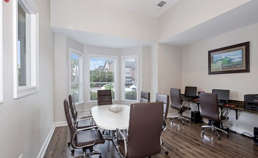 Business center with professional conference table, computers, and printers.