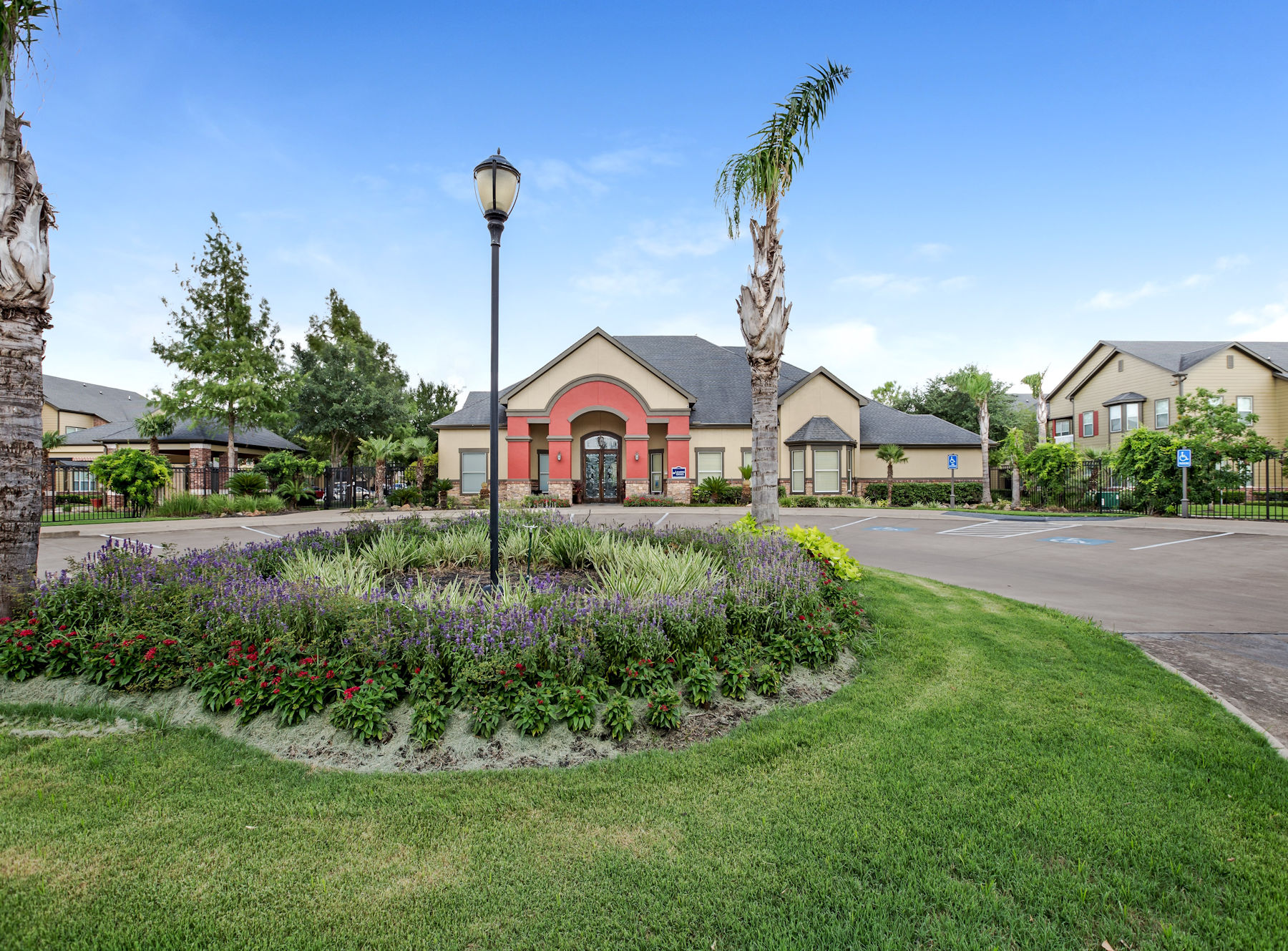 Exterior leasing office with driveway, flowers, grass, trees, and bushes.