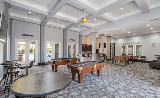 Clubhouse game room with billiards, Foosball, and big screen TV.
