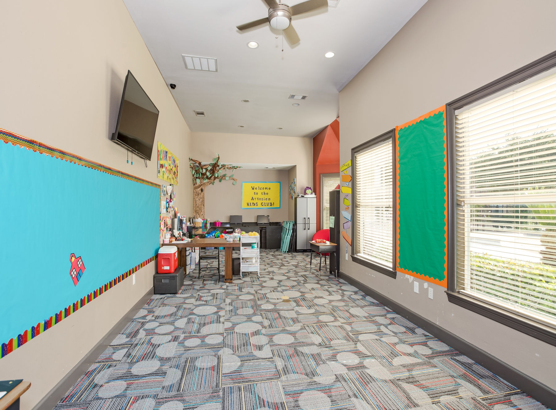 Project access room with windows, TV, chalkboard, and tables, the perfect environment to foster learning.