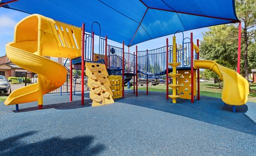 Covered playgound with slides, climbing wall, and jungle gym.
