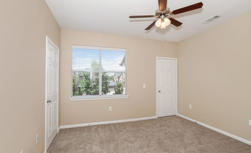 Model bedroom with large window, ceiling fan, and carpeting.