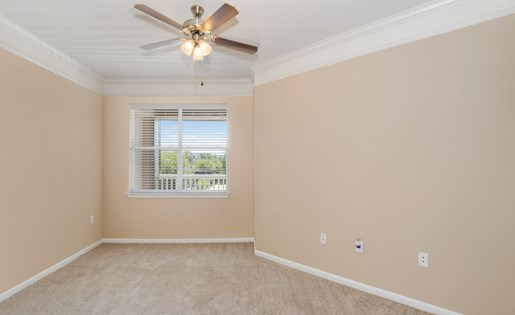 Model bedroom with carpeting, ceiling fan, and large window.