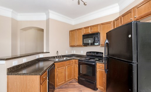 Model kitchen with custom cabinets and black appliances.