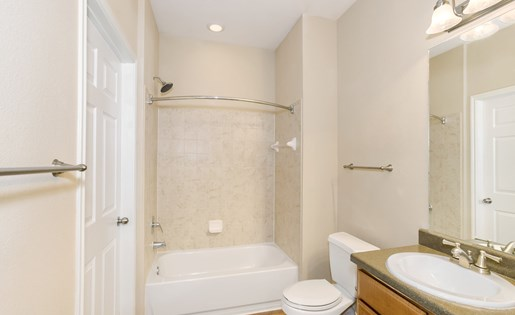 Model bathroom with wood floors, large tub, and modern finishes.