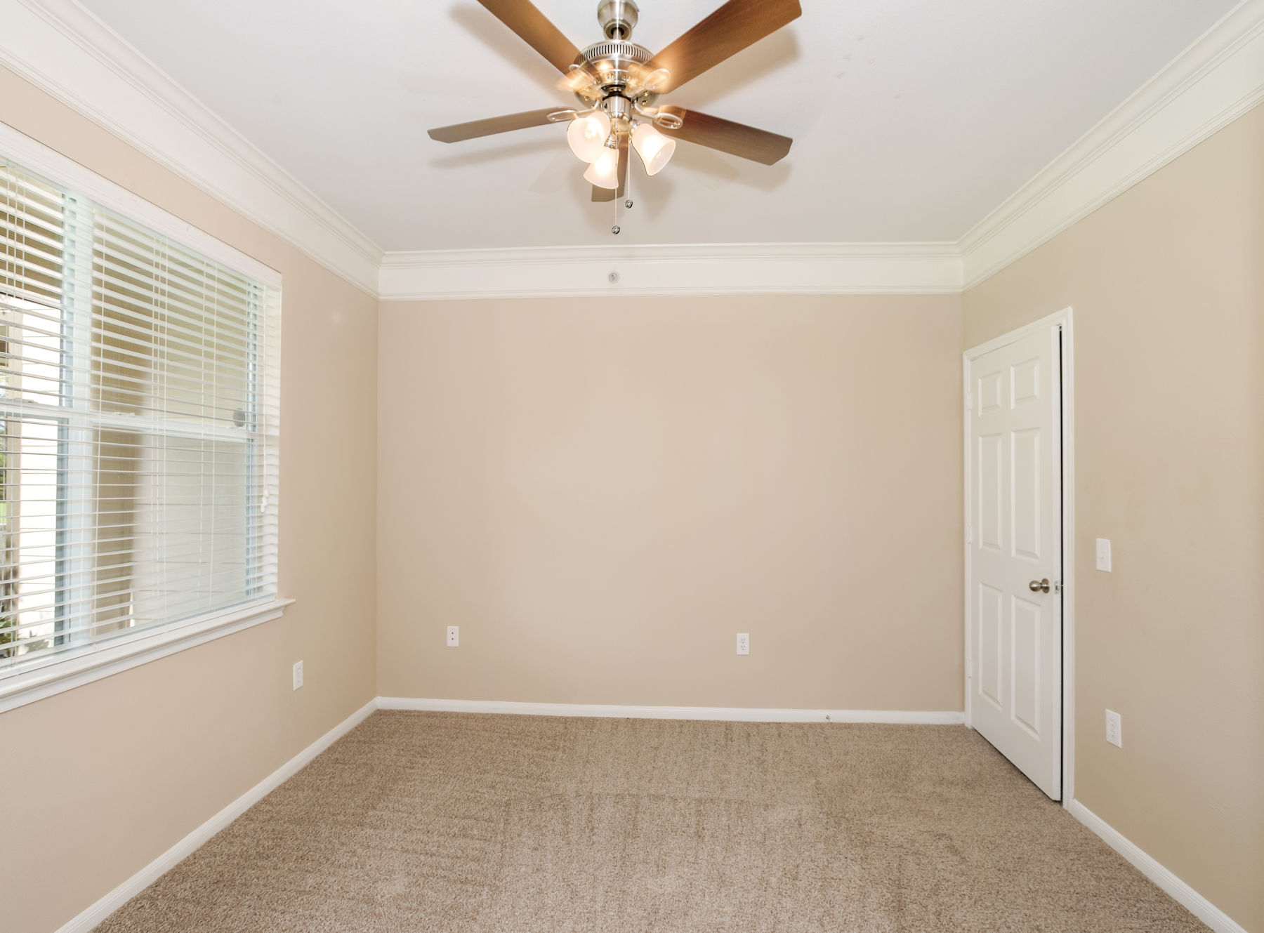Model bedroom with ceiling fan, large window, and carpet.