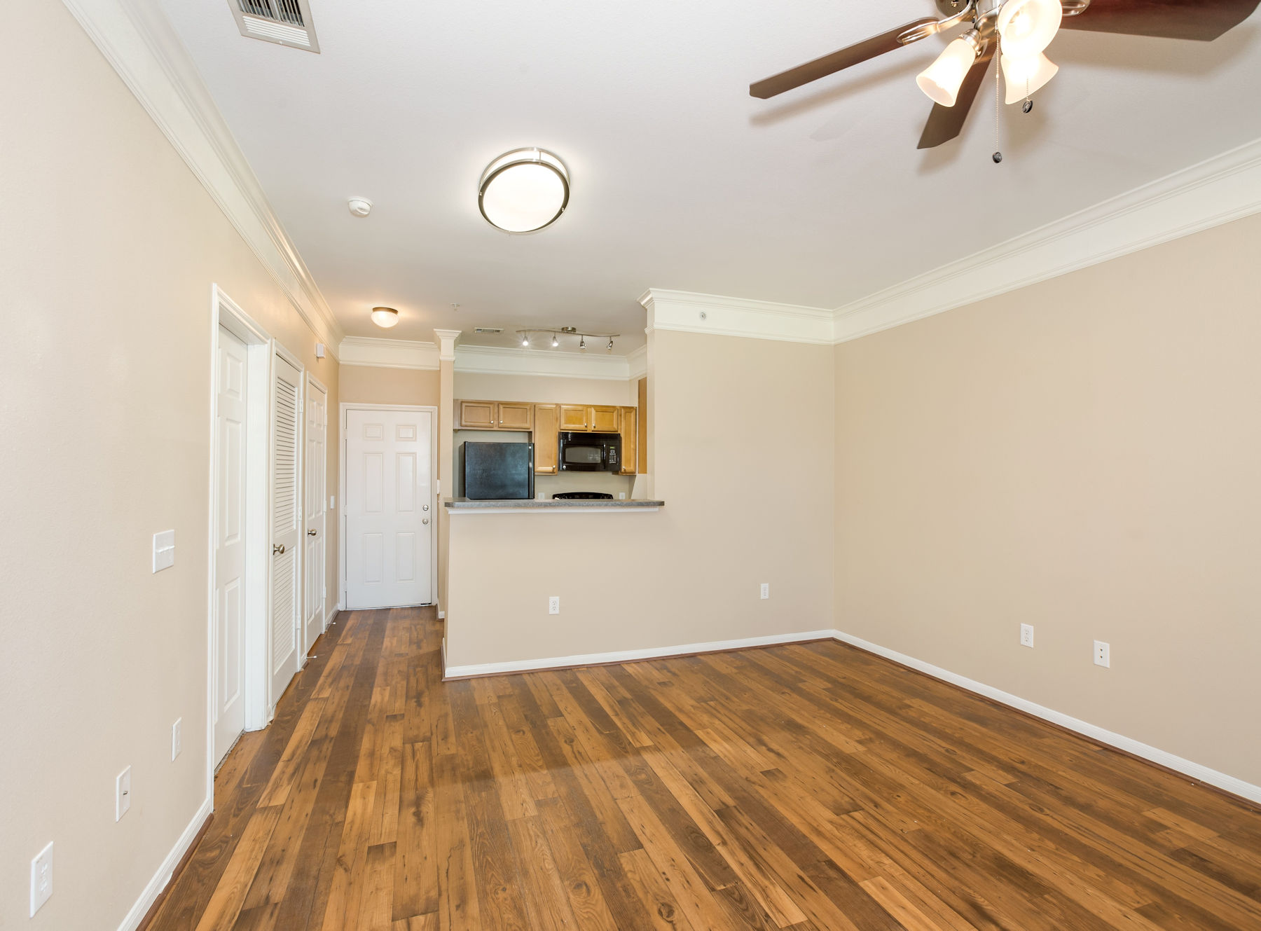 Model living room with wood floor, ceiling fan, and modern paint.