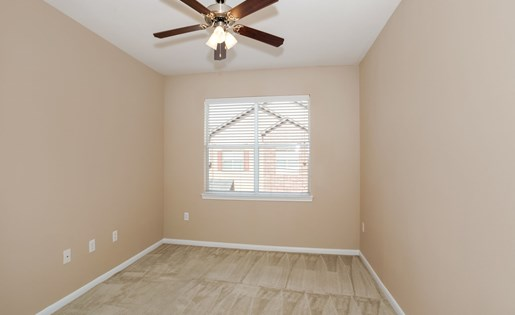 Model bedroom with carpet, ceiling fan, and large window.