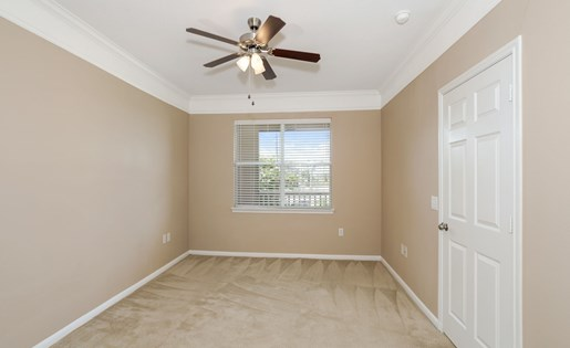Model bedroom with large window, ceiling fan, and carpet.