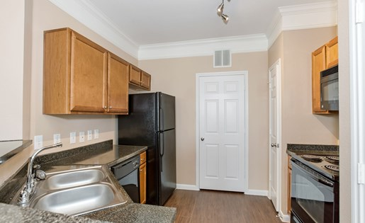 Model kitchen with custom cabinets, wood floor, and black appliances.