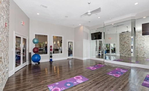Calm yoga room with wood floors, mirrors, yoga mats, and peaceful paint colors.