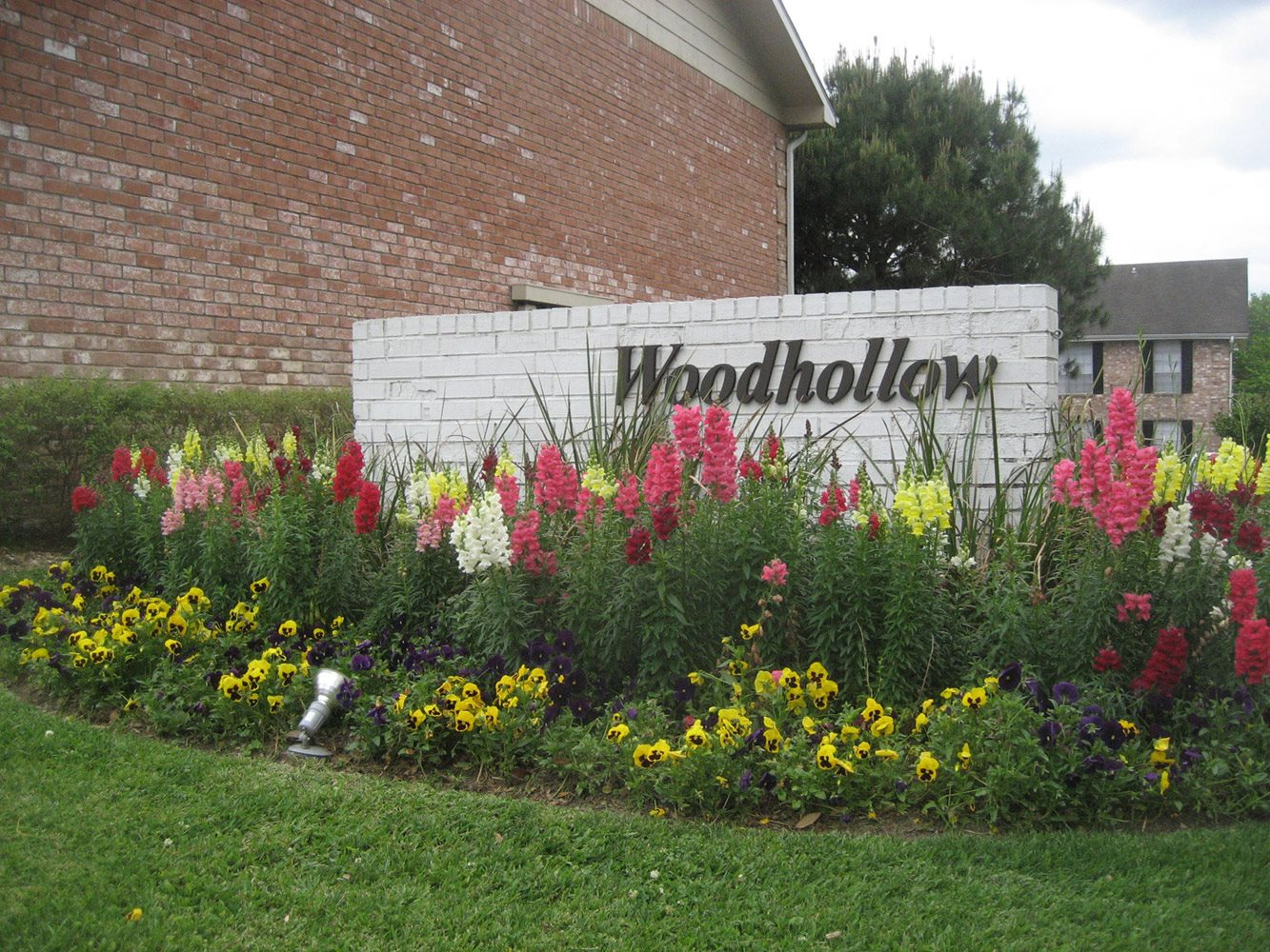 Property Entrance Sign at Woodhollow Apartments in Huntsville , TX 77340
