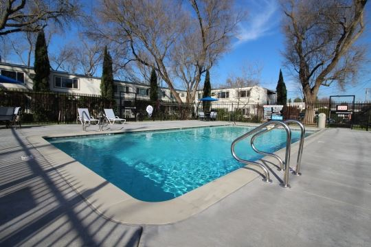 Pool with lounge chairs l Academy Lane Apartments in Davis CA