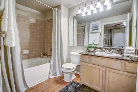 Master bathroom with soaking tub, tile backsplash, large mirror and wood style flooring