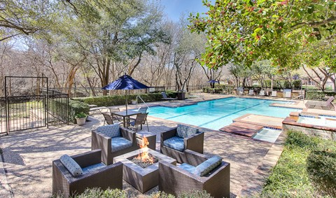 Stunning, tree-lined swimming pool and hot tub with fire pit, tanning deck and lounge seating