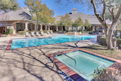 Stunning, tree-lined swimming pool and hot tub with tanning deck and lounge seating