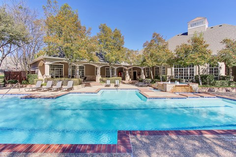 Stunning, tree-lined swimming pool with tanning deck and lounge seating