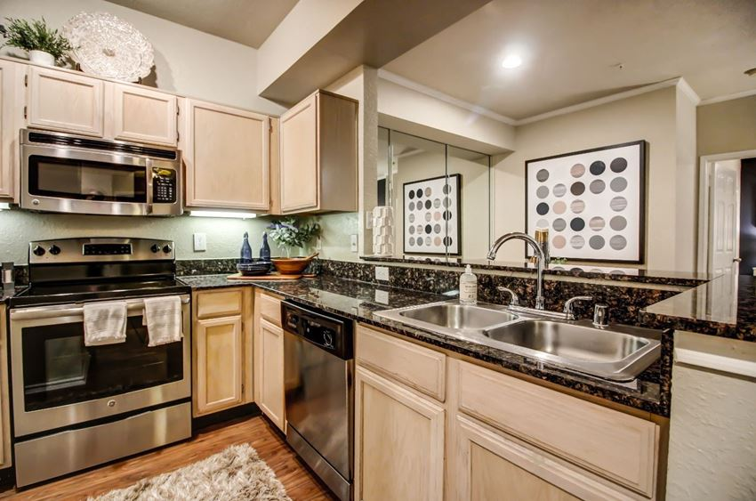 Stunning kitchen with hardwood style flooring, light colored cabinetry and stainless steel appliances