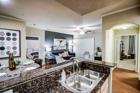 Kitchen are and living room with cozy dining nook, double sink and hardwood style flooring