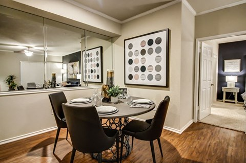 Cozy dining nook with hardwood style flooring, crown molding and wall mirror
