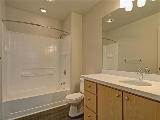 Well-lit bathrooms with curved shower rods to maximize space at Allegro at Jack London Square, CA 94607