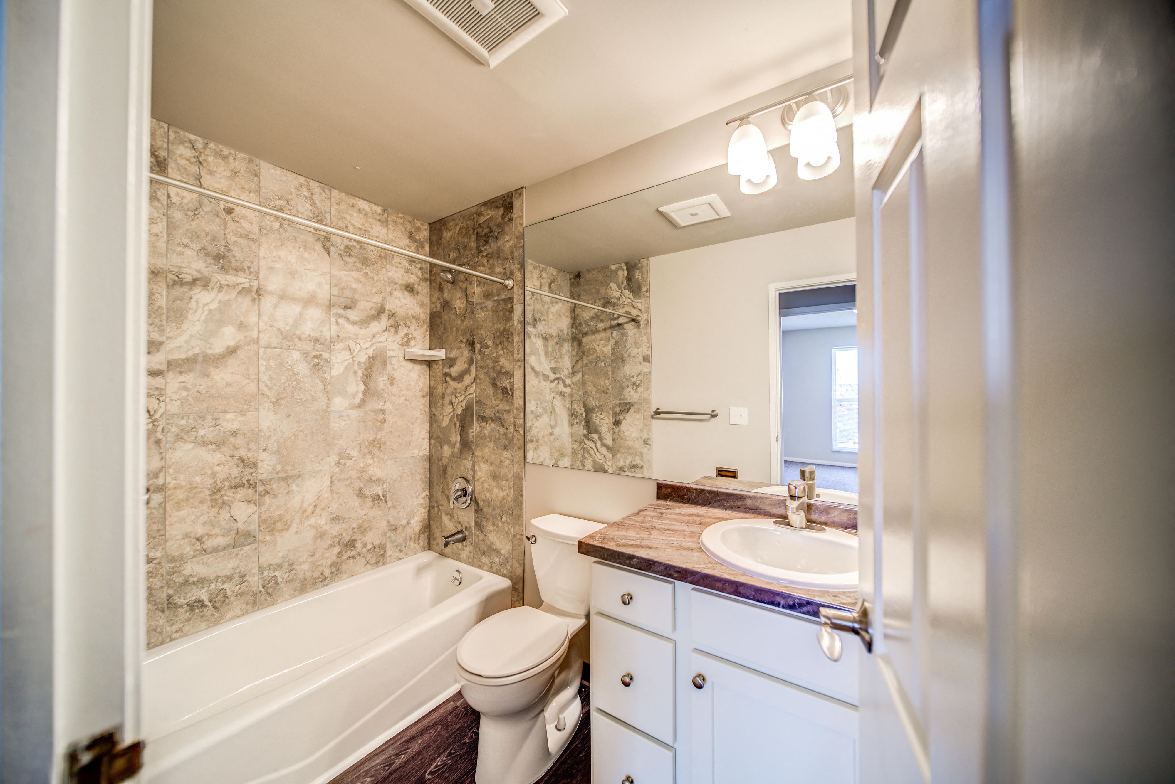 Tiled Bathroom with Tub and White Cabinets