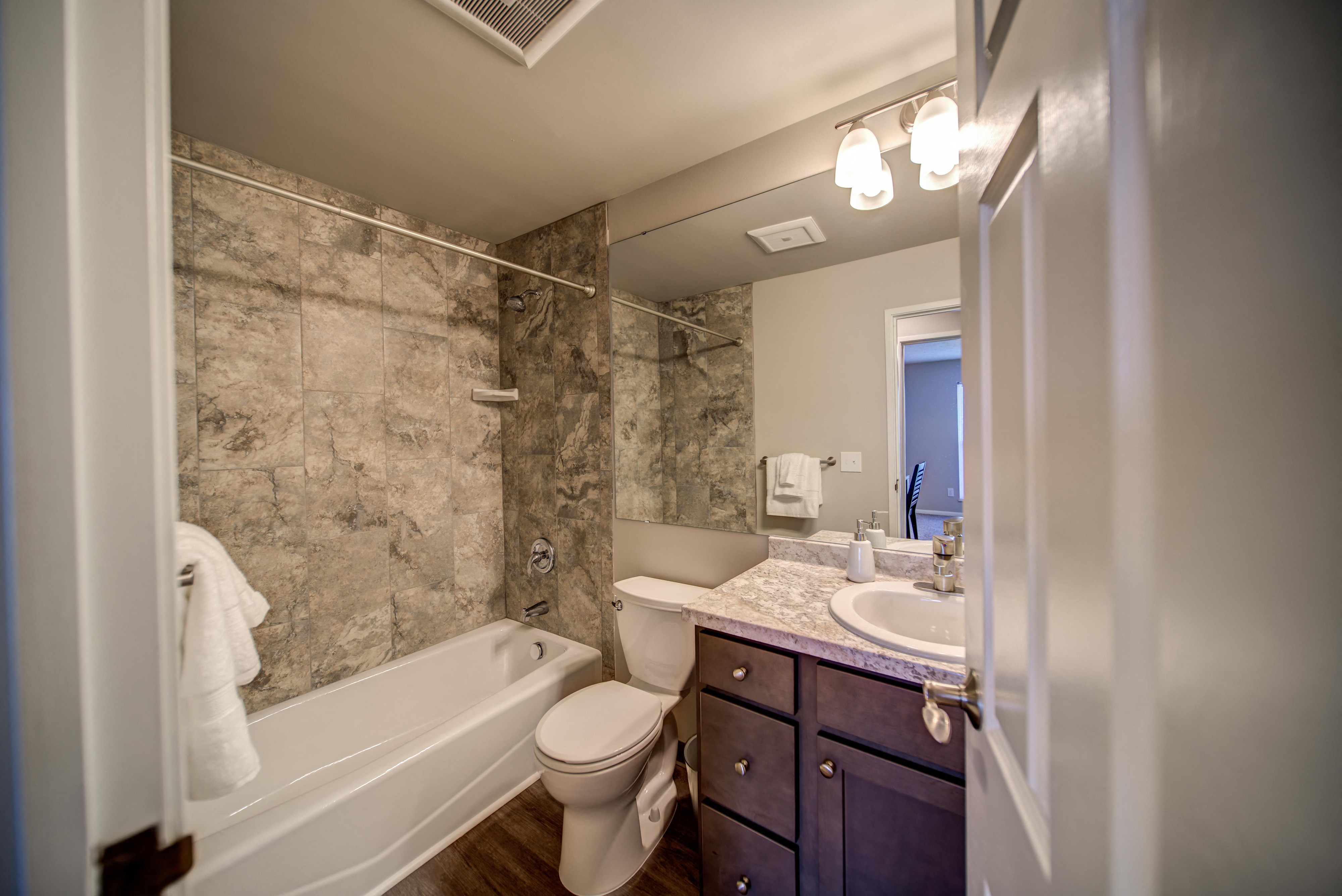 Tiled Bathroom with Tub and Dark Cabinets