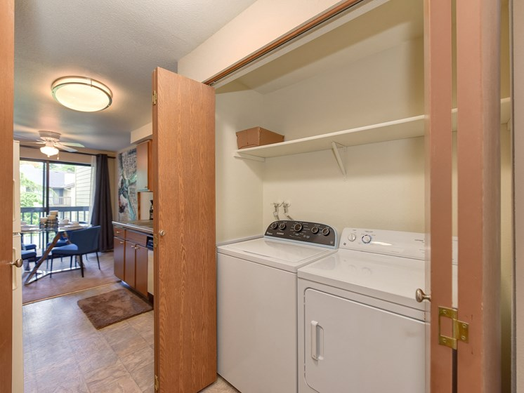 In Unit Washer and Dryer, Wood Cabinets, Shelves and View of Dining Room