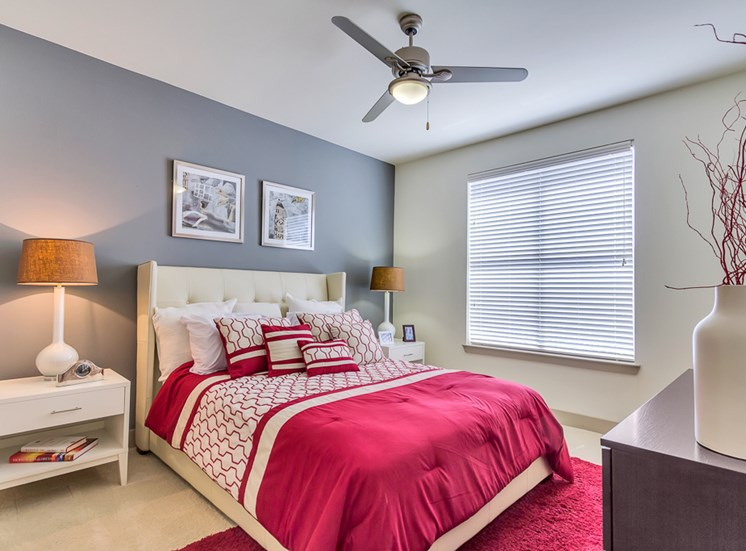 Furnished, carpeted bedroom with queen bed, two nightstands, a dresser. Room equipped with ceiling fan.