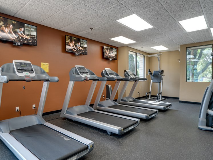 Fitness room with treadmills facing TVs on an orange wall