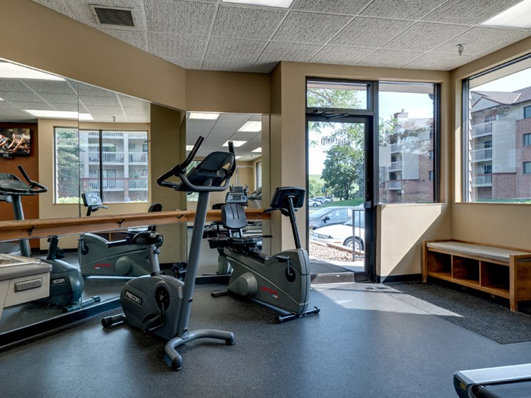 Fitness room with various equipment and a large mirror wall