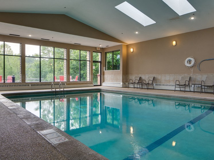 Indoor pool with high ceiling and lounge seating