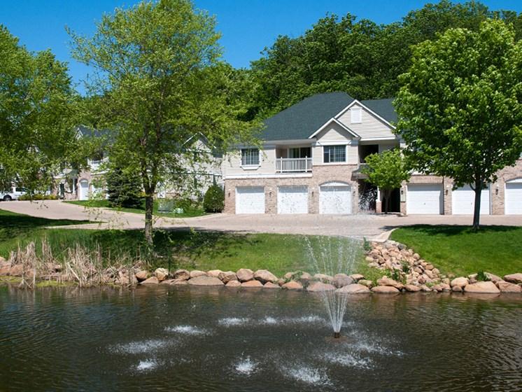 Townhome overlooking a lake with a fountain in it