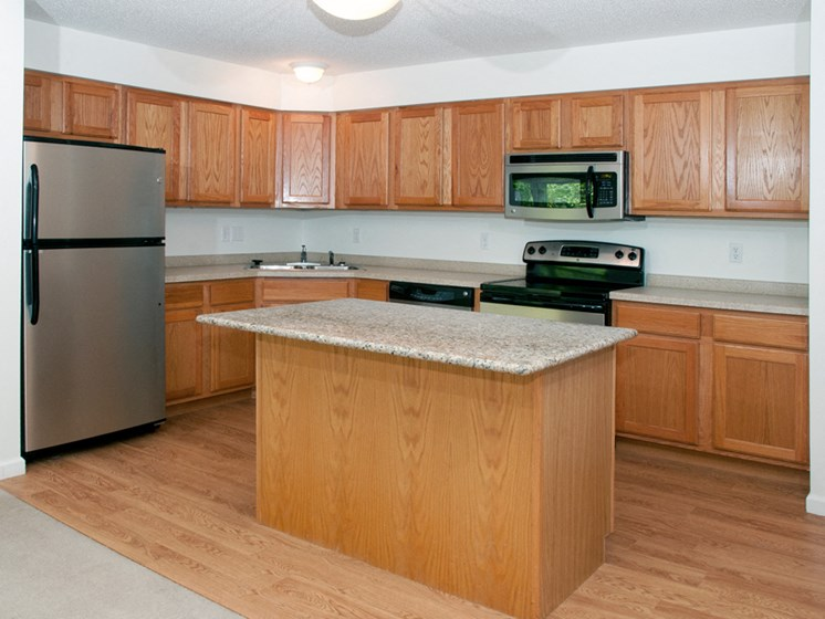 Kitchen with brown wooden cabinets, sand colored countertops, and stainless steel appliances