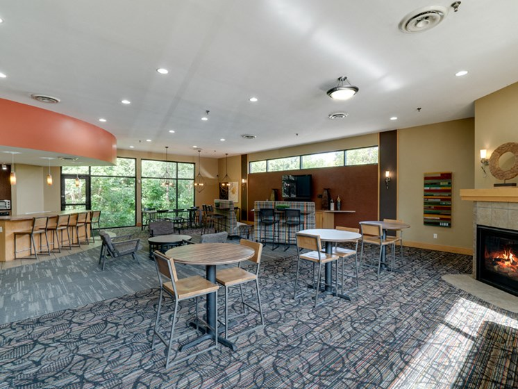 Community room with a variety of seating and tables and a fireplace
