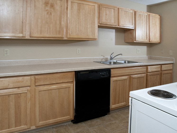 kitchen with wood cabinets, black dishwasher, white oven, and a sink