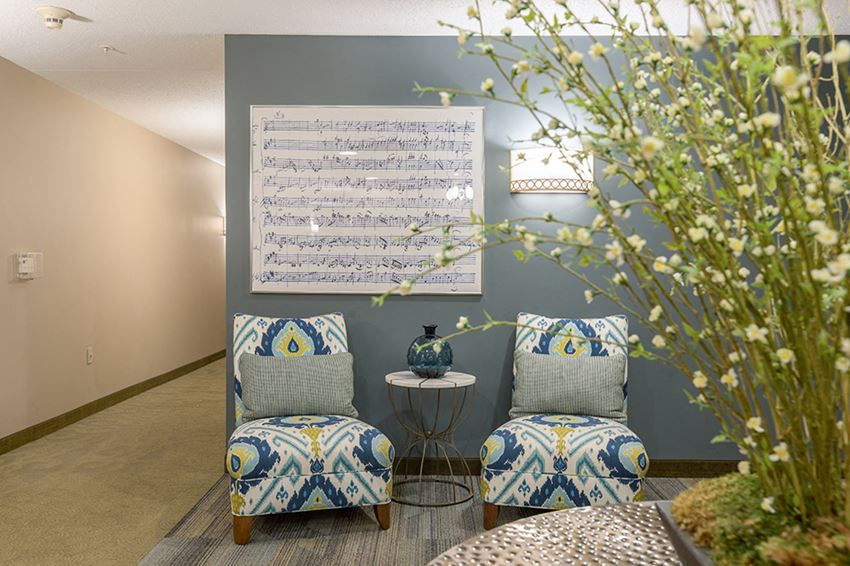 Apartment entryway with seating, artwork, and a large plant