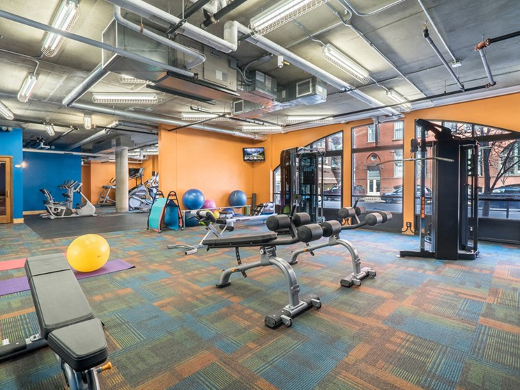 Fitness room with orange and blue walls and lots of different equipment