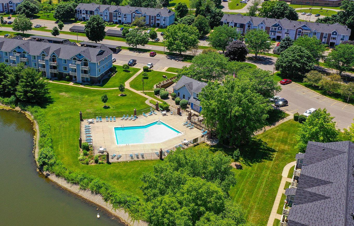 Aerial View of Pool, Lake, and Apartments at Pine Knoll Apartments, Michigan
